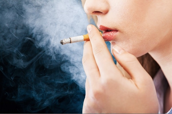 woman smoking, which may increase her risk of serious eye conditions
