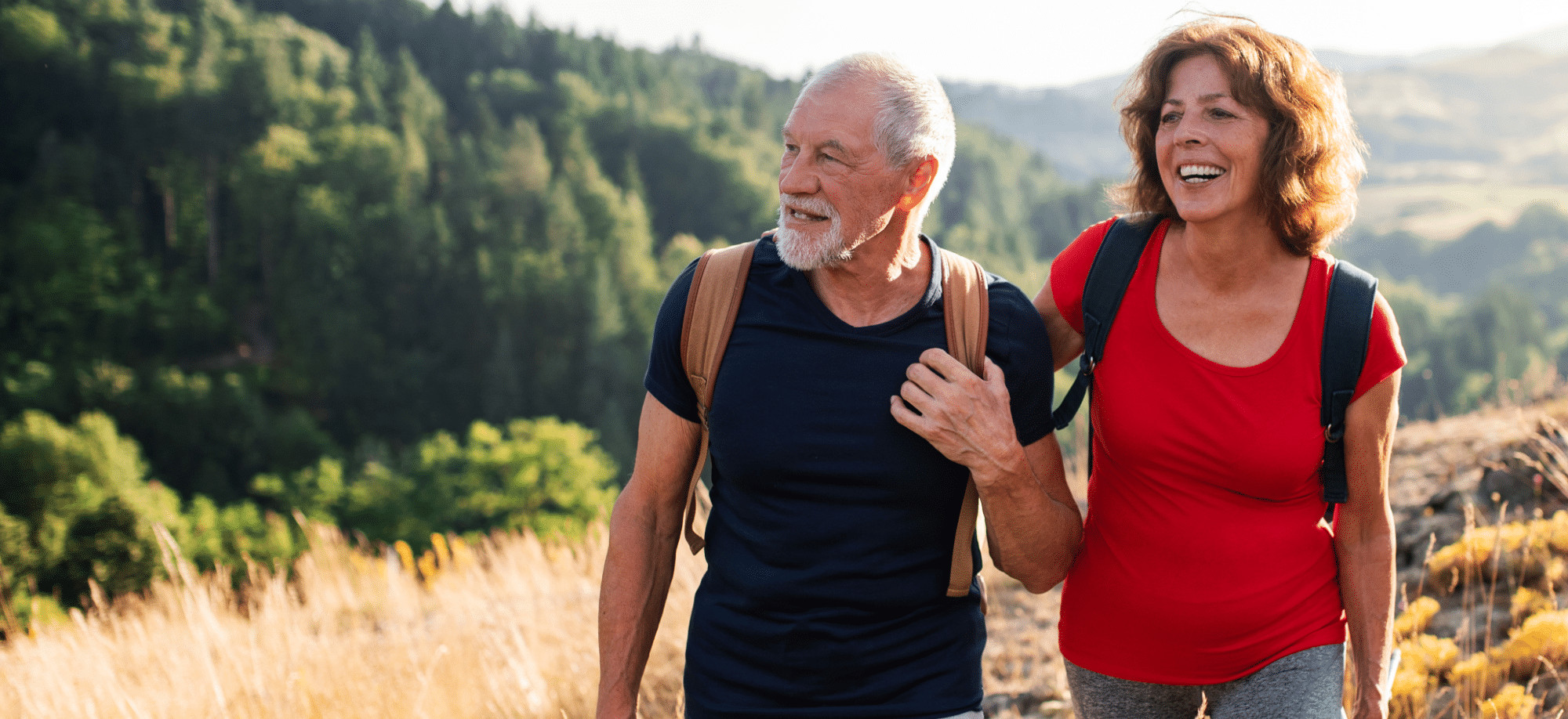 senior tourist couple travellers hiking in nature walking and talking