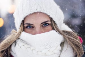 A young woman bundled up in the snow in a white hat and scarf