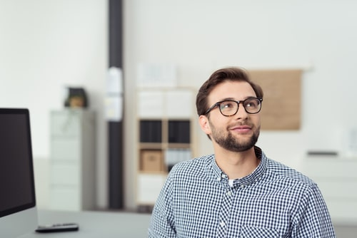 A young professional man at the office sites in front of his desk and computer screen while wearing glasses and looking up toward the back of the room